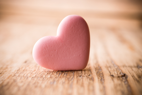 Pink heart-shaped candy on a wooden background.