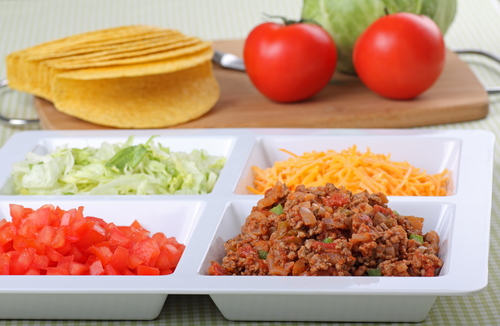 Beef, tomato, lettuce, cheese and shells for making tacos