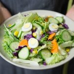 Hands holding out a keto friendly salad on a white plate. Salad has lettuce, cucumbers, hard-boiled eggs and no dressing.