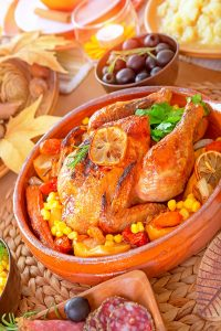 oven roasted chicken surrounded by fresh vegetables on a wooden able with fruit in the background.