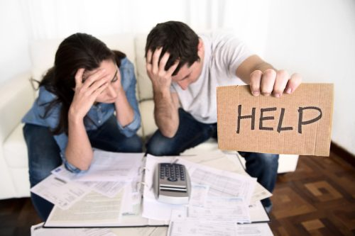 in debt; young couple worried need help in stress at home couch accounting debt bills bank papers expenses and payments feeling desperate in bad financial situation; image licensed from Deposit Photo by Lori Soard