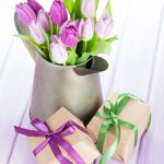 easter party ideas; Purple tulip bouquet in watering can and gift boxes on wooden table pretty and feminine decorations for easter.