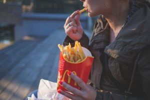 Image of young woman eating a large McDonald's French fry. She is holding the fries in her left hand and eating one of them with her right. She wears a lightweight jacket and appears to be outside on bleachers.