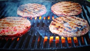 hot outdoor grill with fire under grate and partially grilled hamburger patties on top. Steam rises from the food.