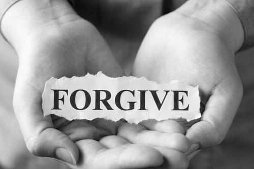 "Torn piece of paper with the word ""Forgive"" in the woman's palms. Black and White."