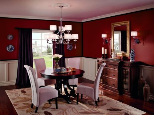 Dining room decor shows a room in a deep brick red with white wainscoting around the bottom of the wall. There is small, round table with four white chairs and flowers in the center of the table. A wooden dresser with a golden mirror over it is to the right.
