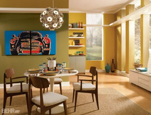 This feng shui dining room design is set in a mustard yellow and olive green room with a white plastic table and four wooden padded modern chairs. Everything sits on a neutral tan rug.