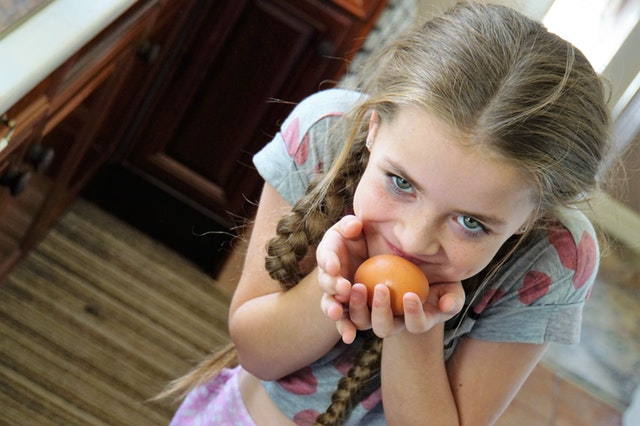 Pretty little brown-haired girl with blue eyes eating an orange