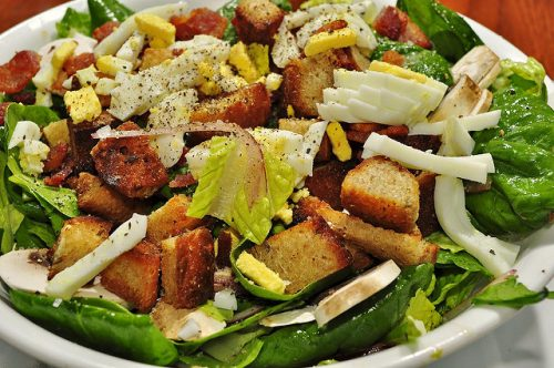 Salad in white bowl with fresh greens, thin slices of hard-boiled egg, and homemade croutons.