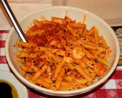 Round white bowl of penne pasta with shrimp and tomato sauce sitting on a red and white checkered tablecloth.