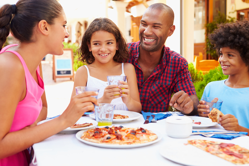 Image shows a amily sitting around an outdoor cafe table with a white tablecloth. Dad is in the center with daughter on his lap. Mom is to the left in a pink dress. Son is to the right in a blue tee shirt. They are all smiling at each other and enjoying pizza and glasses of water.