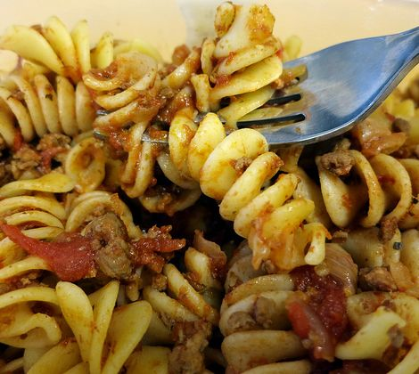 Closeup view of spiral pasta with meat and tomato sauce and a fork coming in from the top right.