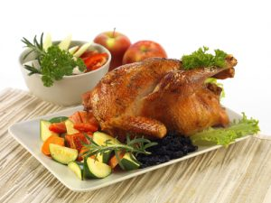 Wooden table featuring a white plate with a large turkey surrounded by squash and zucchini. In the background is a bowl with greens and tomatoes and behind that two red apples.