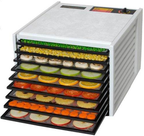 White food dehydrator on blank background. Tras are pulled out at varying depths and you can see fruits and vegetables being perserved, including apples, carrots, pineapples, tomatoes, oranges, cucumbers, mushrooms, corn and peas.