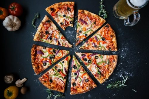 A whole pizza with slices separated from one another to leave a little space between each one. The slice at the top has a bite out of it. The pizza has veggies and olives and sprigs of greenery around the edge of the pizza.