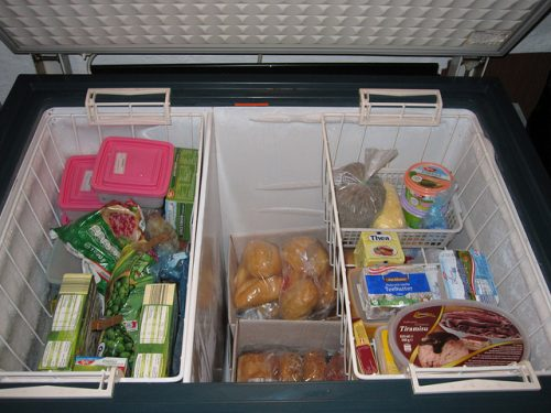 Photo of the inside of a chest style freezer. There is a basket filled with frozen items on each side. You can see rolls, vegetables and other items inside the freezer.