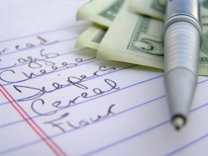closeup of shopping list written on white school paper, money and pen in the background.