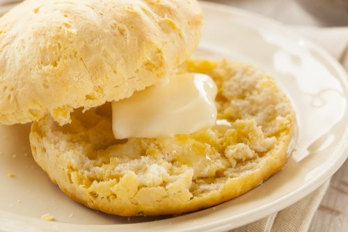 Delicious, fluffy buttermilk biscuit cut open and with butter dripping in the middle - mouthwatering biscuit