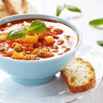 Tasty soup recipe in a light blue bowl on a white place with a small piece of bread on the side. Community hobo stew or mulligan stew.
