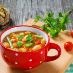 Tasty soup recipe in a red bowl with handle and small white polka dots sits on a wooden board with fresh cherry tomatoes scattered about.