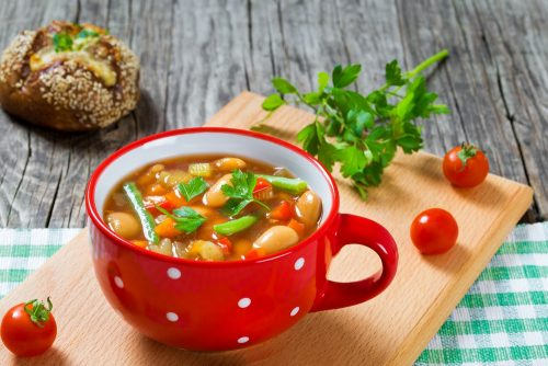 Tasty hobo soup recipe in a red bowl with handle and small white polka dots sits on a wooden board with fresh cherry tomatoes scattered about.