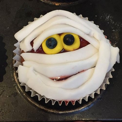 Mummy cupcake with berry glaze and vanilla icing.