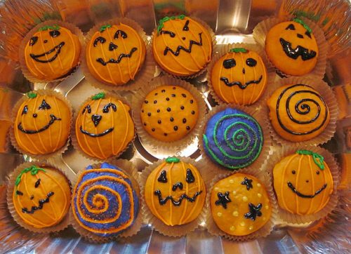 Collection of pumpkin shaped cupcakes with jack-o-lantern faces designs.