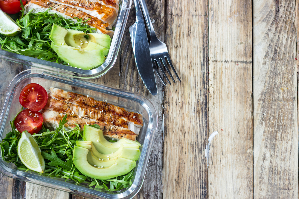 Healthy meal prep containers with rukola, turkey grill, tomatoes and avocado Meal prep ideas.